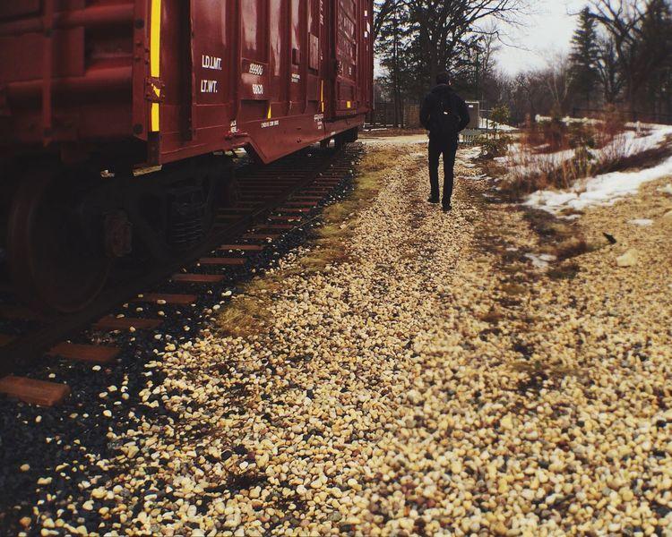 Man In Black Walking Along Side Train Tracks Train On Track Gravel Walk Walking Away Urban Spring Fever