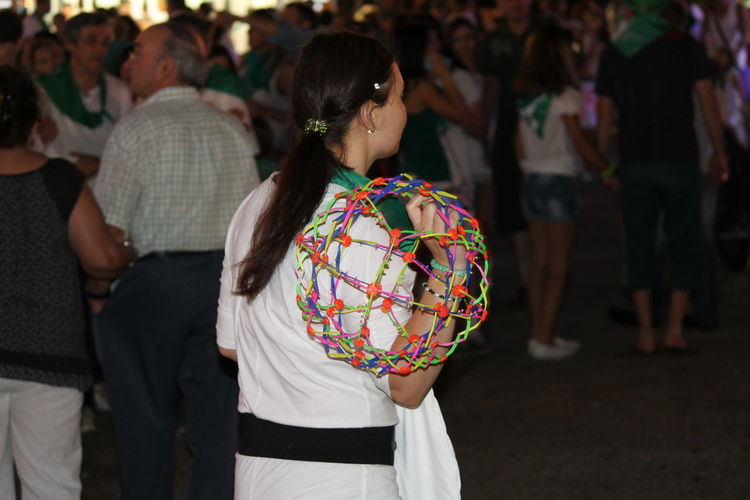 Rear view of woman carrying colorful toy