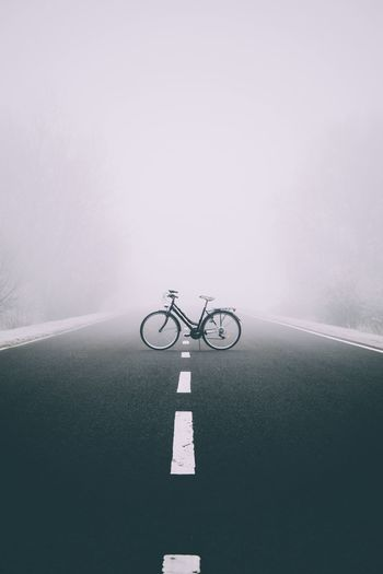 Bicycle Parked On Road During Foggy Weather