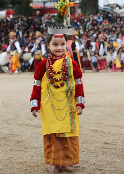 Girl In Traditional Costume Standing Against Crowd During Celebration