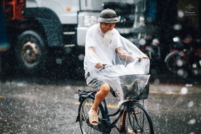 Man riding bicycle on road in rain