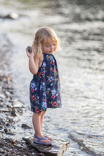 Full Length Of Cute Girl Holding Rock At Riverbank