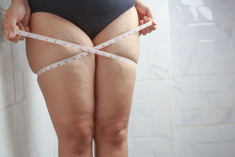 Midsection of woman standing on tiled floor