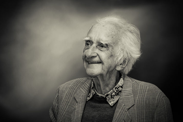Portrait of smiling mid adult woman against gray background
