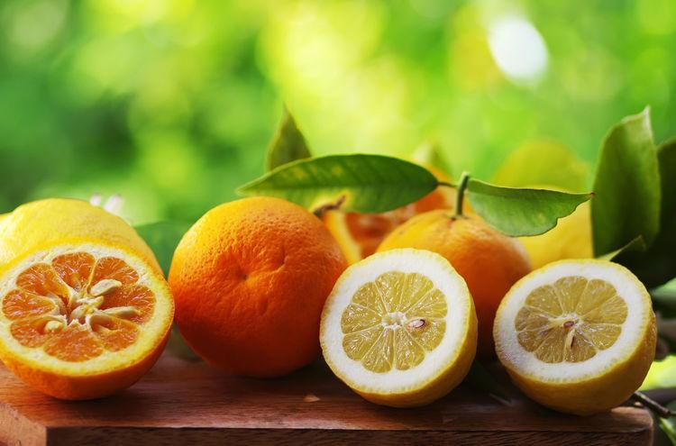 Citrus Fruit with leaves on green background Citrus Fruit Close-up Food Food And Drink Fruit Green Color Healthy Eating Leaf Lemon Orange Orange - Fruit Orange Color Ripe SLICE Sour Taste Table