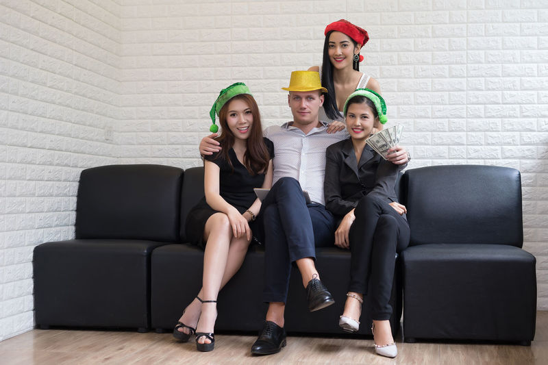 Portrait of friends wearing hats on seats against white brick wall