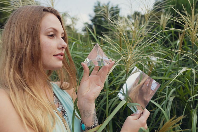 Young woman holding prism and mirror while standing against plants