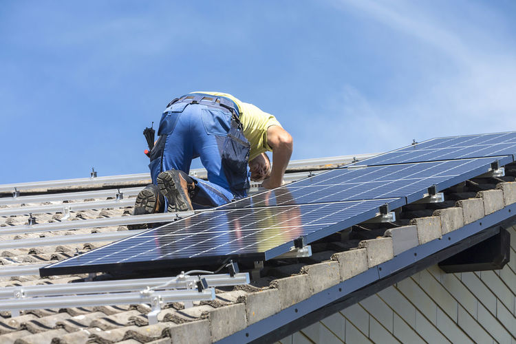 Low angle view of man installing solar panels on roof against sky