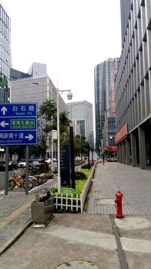 Road sign on footpath by buildings against sky
