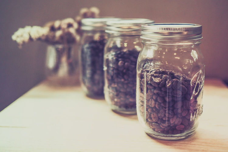 Close-up of coffee beans in glass jars on table