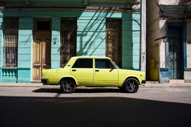 Yellow car on street against building. havana, cuba