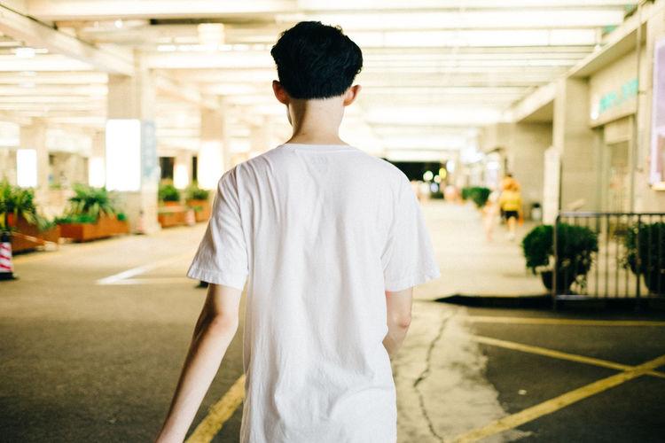 Rear view of man standing in corridor