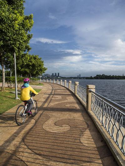 Person Biking On Boardwalk Against Sky