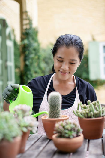 Woman watering succulent plant at workshop