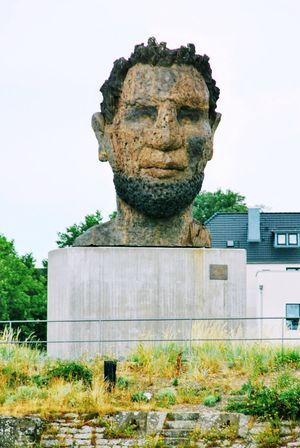 Poseidon in Ruhrort No People Harbour Cruise Statue Lüpertz 5 Meter Large Pixelated Human Face Tree Portrait Statue Architecture Sky Green Color Sculpture Sculpted Art And Craft Art