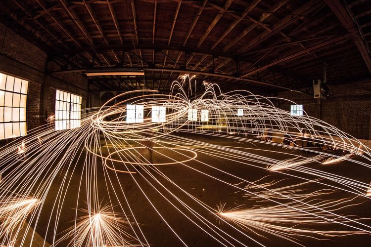 Person spinning firework in empty warehouse