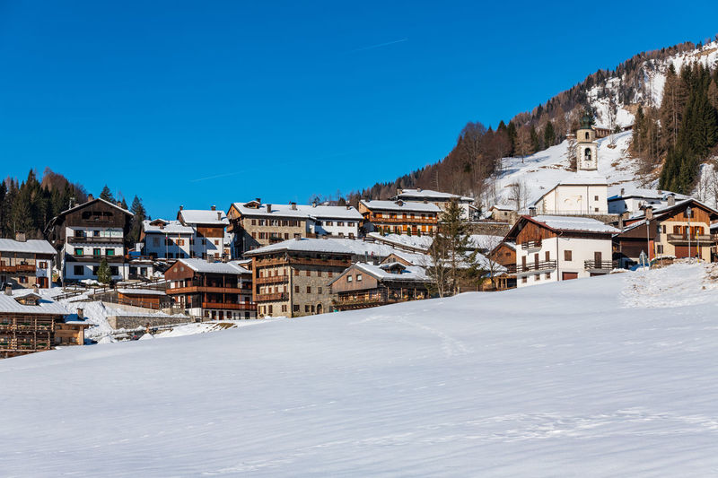 Winter in sauris di sotto. traditional architecture under the sun and snow
