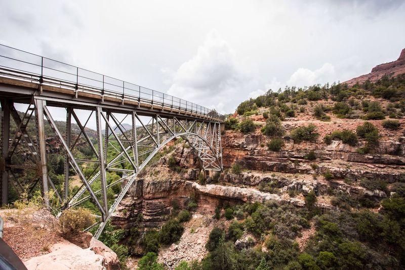 Arch bridge over landscape against sky