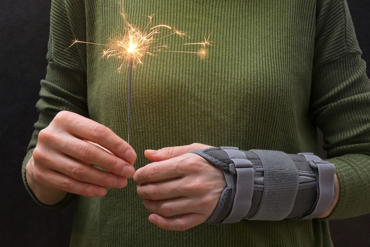 Midsection of woman holding illuminated sparkler with bandage on hand