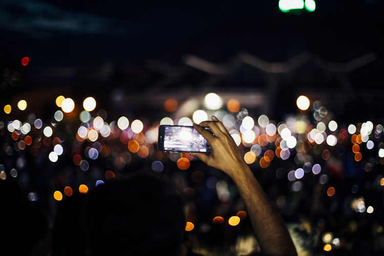 Low angle view of hand holding illuminated smart phone at night
