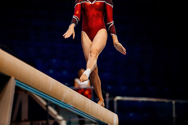 Low section of gymnast standing on wooden plank