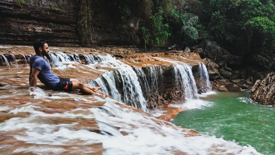 Man Sitting On Waterfall At Forest