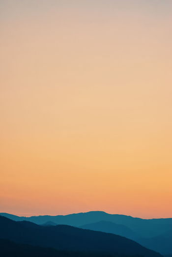 Amazing mountain landscape and orange sky at sunset time Beauty In Nature Clear Sky Copy Space Environment Idyllic Landscape Mountain Mountain Range Nature No People Non-urban Scene Orange Color Outdoors Remote Romantic Sky Scenics - Nature Silhouette Sky Sunset Tranquil Scene Tranquility