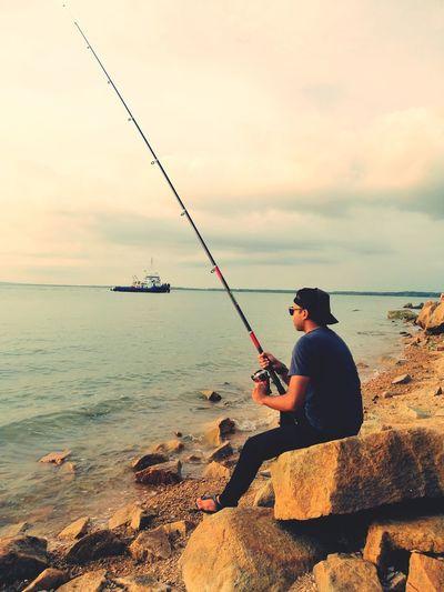 Man Fishing While Sitting On Rock At Beach