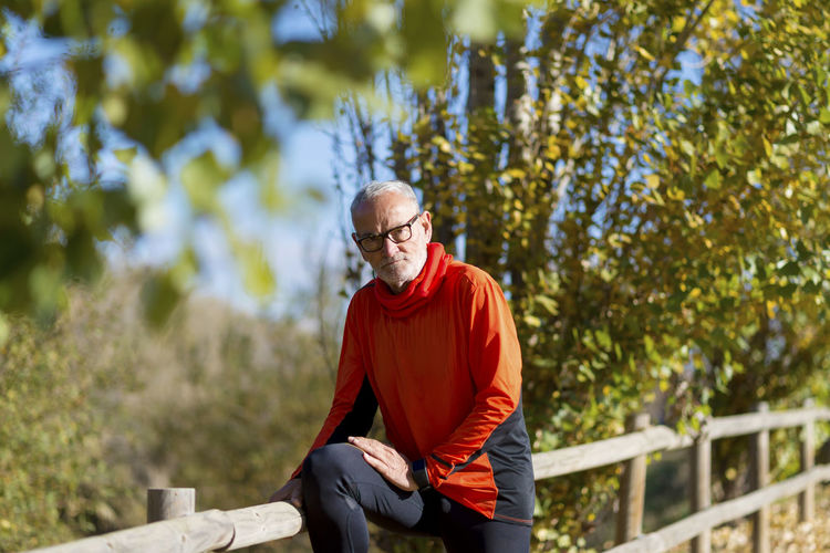 Portrait of senior man leaning on fence in park