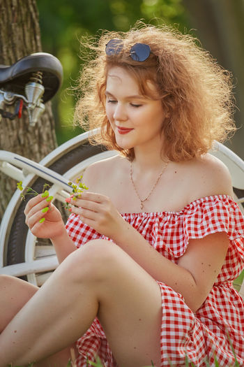 Midsection of woman holding while sitting outdoors