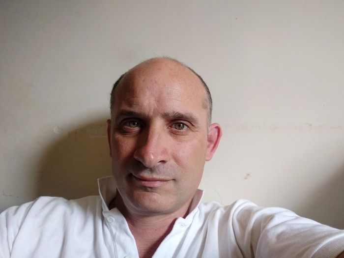 Close-Up Portrait Of Balding Mature Man Against Wall At Home