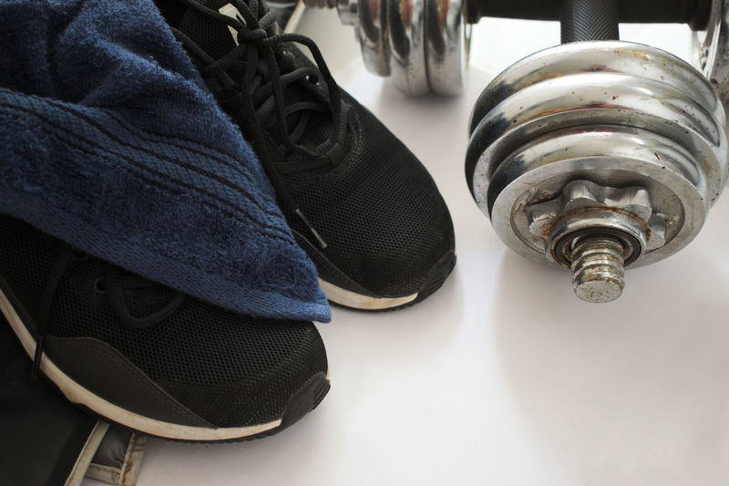 High Angle View Of Sports Shoe With Dumbbell On Floor