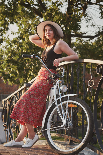 Beautiful pinup girl in skirt and hat posing with bike in sunny park in sun light