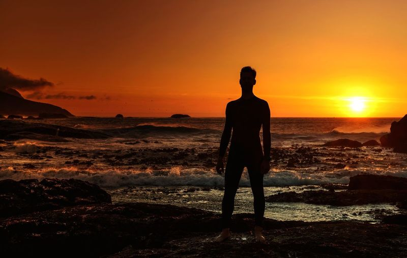 Lost In The Landscape Sunset Silhouette Orange Color Beauty In Nature Nature Standing One Person Scenics Real People Sky Sun Tranquil Scene Sunlight Lifestyles Sea Outdoors Tranquility Leisure Activity Landscape Full Length Lost In The Landscape This Is Masculinity