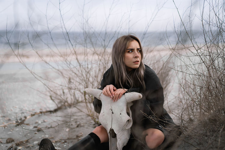 Portrait of beautiful young woman sitting on sand on the beach during winter