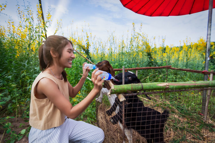 Smiling young woman feeding goat with baby bottle while standing against plants