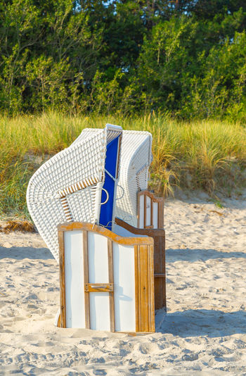 Empty chair on sand at beach