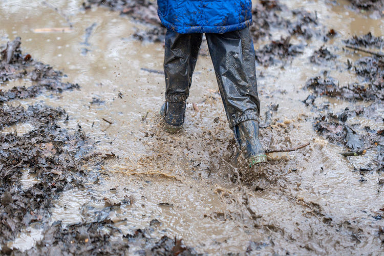 Low section of man standing in mud