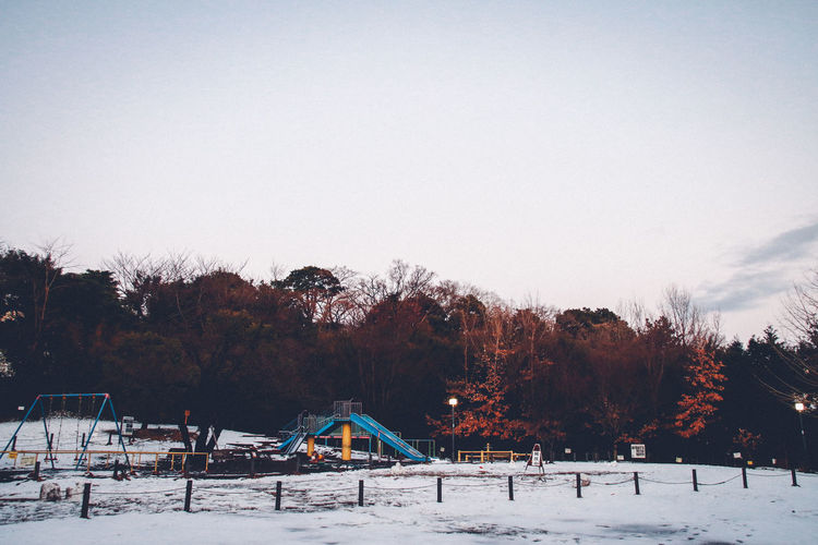 Snow covered playground against sky