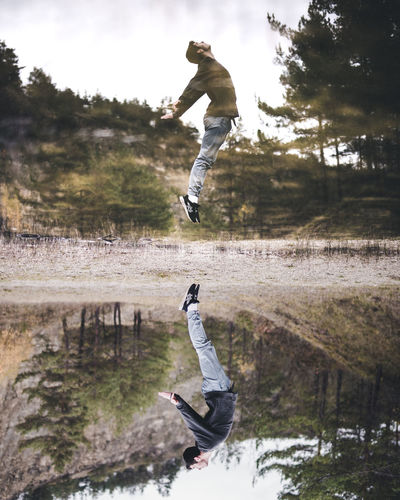 Low angle view of man jumping against trees