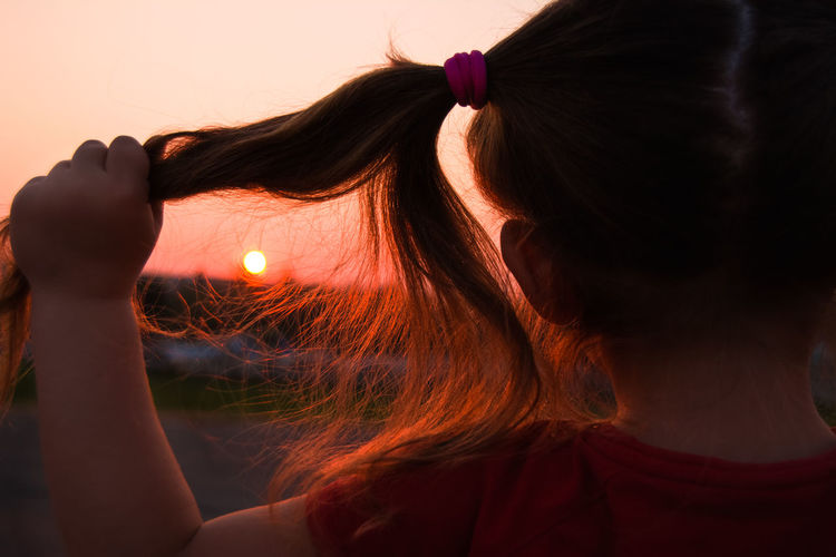 Rear View Of Girl Holding Pigtails During Sunset