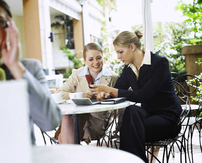 Businesswoman With Colleague Using Phone At Cafe