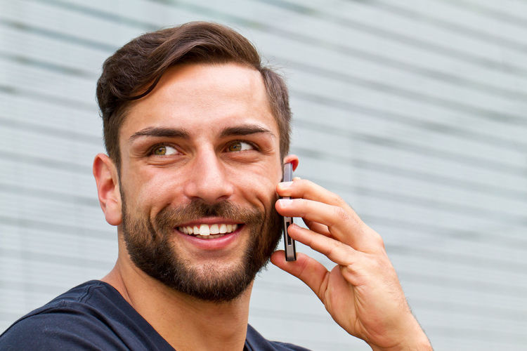 Happy man with smart phone Business Handy Happy Looking Away Man Modern Architecture Young Beard Call Cheerful Communication Finance Handsome Happiness Headshot Leisure Men Outdoors Phone Portrait Smart Phone Smiling Technology Using Phone Young Adult