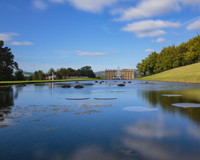 Chatsworth House and the Emperor Fountain from across the Canal Pond in the Peak District National Park Architecture Britain Chatsworth Fountain National Pond Scenic Trees Blue Canal District Emperor England House Landscape Outdoors Park Peak Sky Still Uk Water