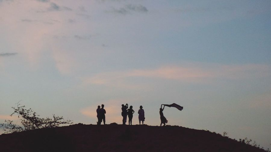 Silhouette people standing on field against sky during sunset