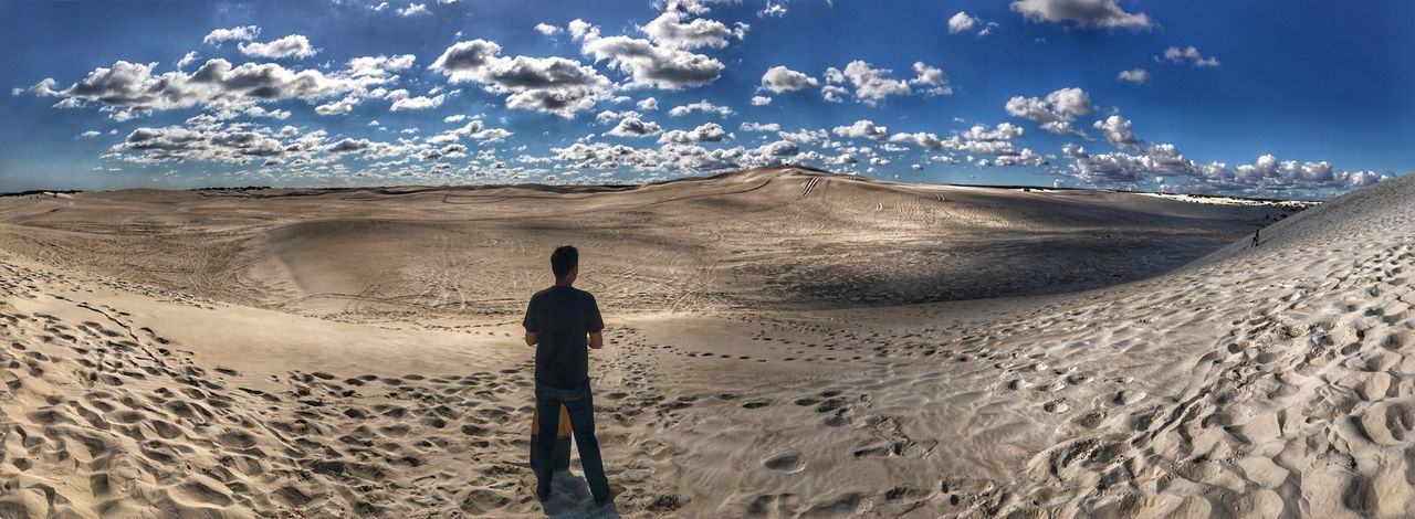 Rear View Of Man Standing On Sand Against Cloud Sky