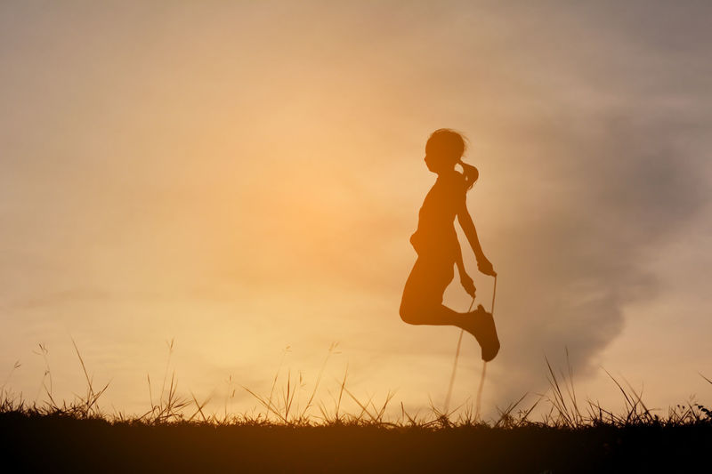 Silhouette Girl Skipping On Field Against Sky During Sunset