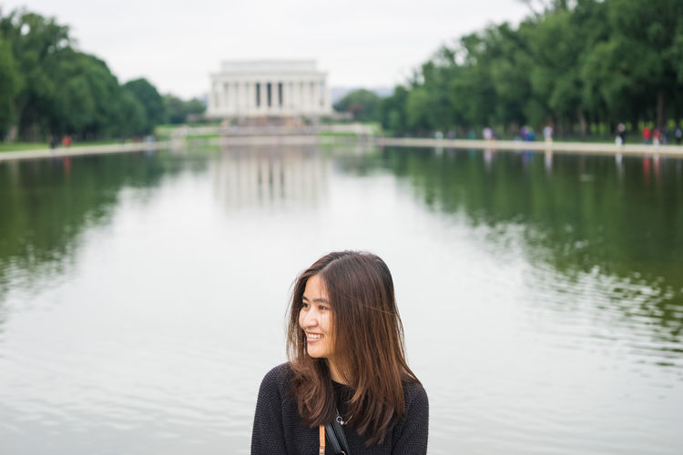 Woman smiling while looking away by reflecting pool