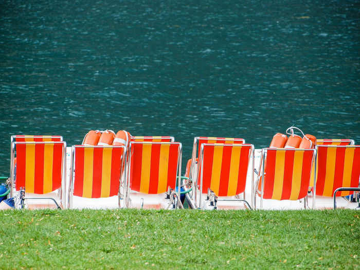 Grass Water Day Nature Land Orange Color In A Row Safety Sea No People Protection Outdoors Side By Side Sunlight Plant Security Seat Chair Field