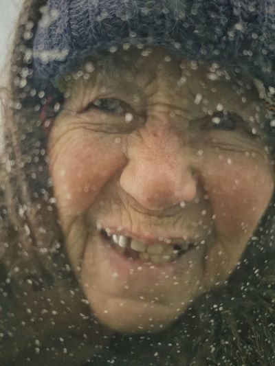 Close-up portrait of smiling woman in wet park during winter